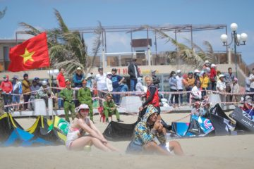 Crowd watches the Phan Rang kiteboarding action take place on windy beach in Vietnam