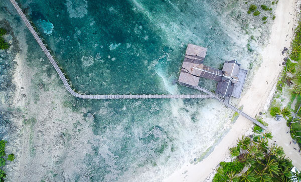 aerial shot of Cloud 9 surf spot in Siargao, Philippines. Aqua blue water surrounds a small jetty and building perched on the shores of the white sand beach