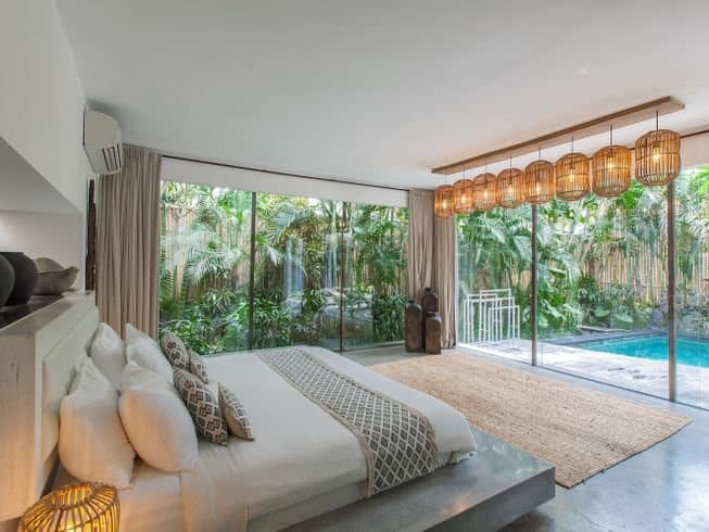 Inside of a bedroom overlooking a private pool at Kima Surf Camp, Bali