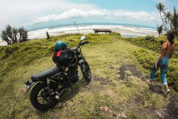 Motorbike parked on grass while girl is checking out a well known Bali surf spot, Medewi