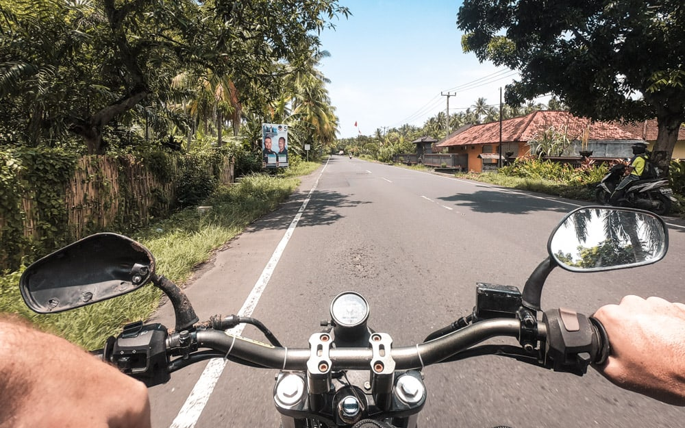 View of motorcycle handlebars while driving down the road during Bali road trip