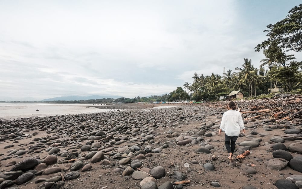 Grace is walking on the black sand scattered with boulders at the Medewi surfing beach. The sky is overcast and looks a little stormy.