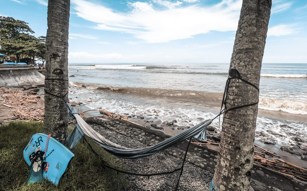 A hammock tied between two palm trees overlooking the surf in medewi, Bali
