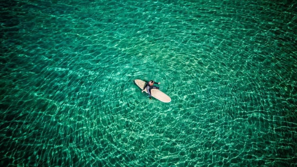 Beautiful surf photography of man sitting on surfboard in clear green water