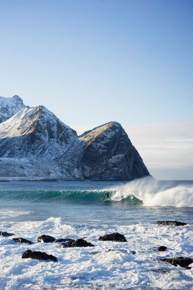 surfing photography from Norway; a wetsuit clad surfer surfs in cold water at base of mountain