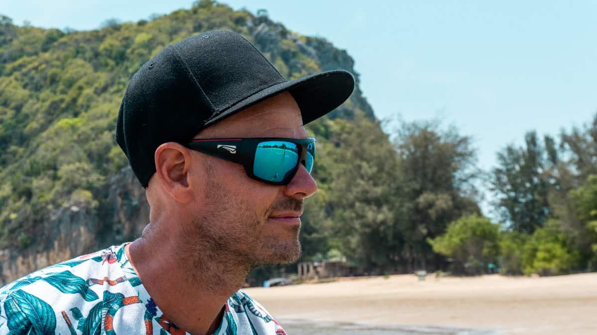 Uomo sulla spiaggia con occhiali da sole di qualità con lenti polarizzate Carl Zeiss