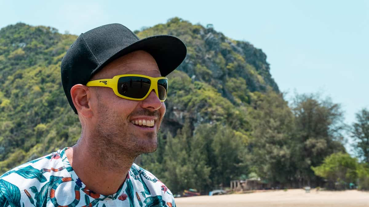 Man smiling while wearing the 'Flo' floating sunglasses in mustard yellow