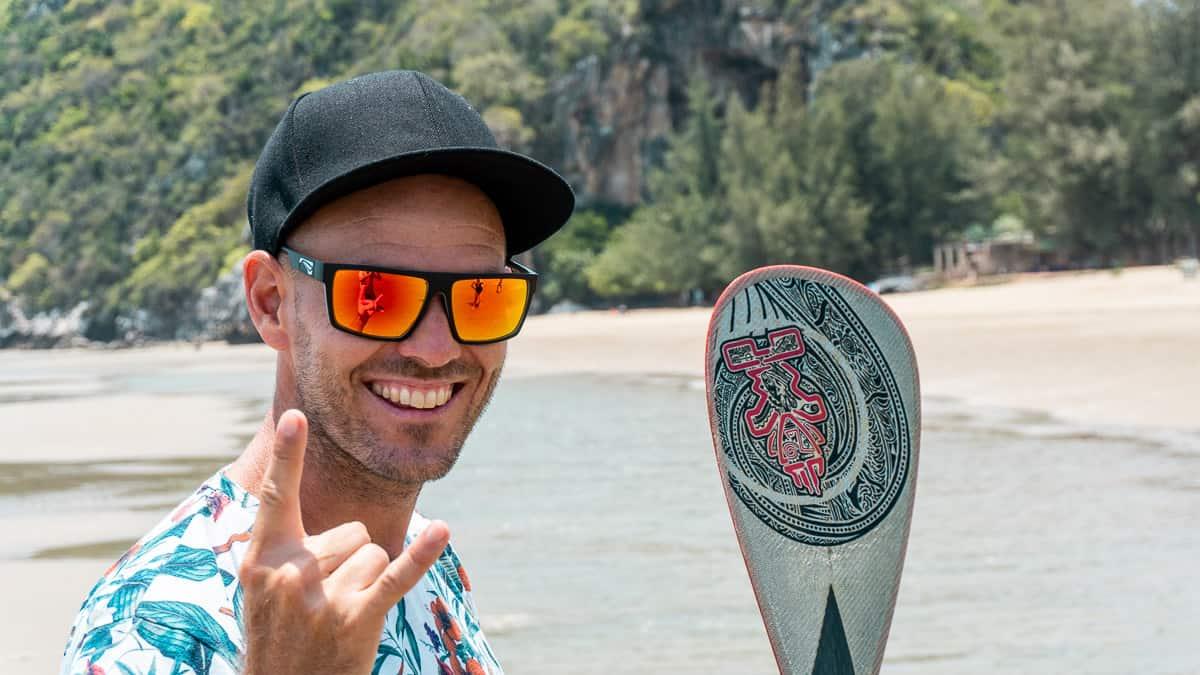 Homme souriant portant les meilleures lunettes de soleil de voyage avec des lentilles Zeiss sur une plage