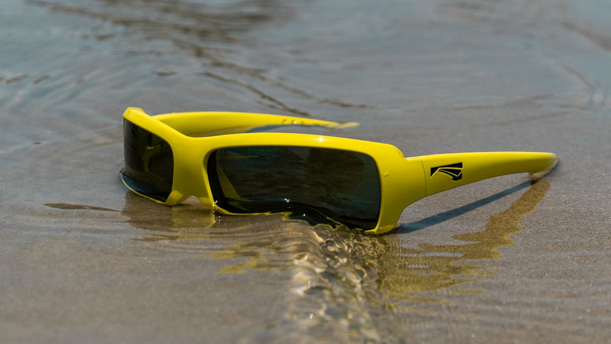 The 'Flo' floating sunglasses by LiP in mustard Yellow on the beach with water flowing over them