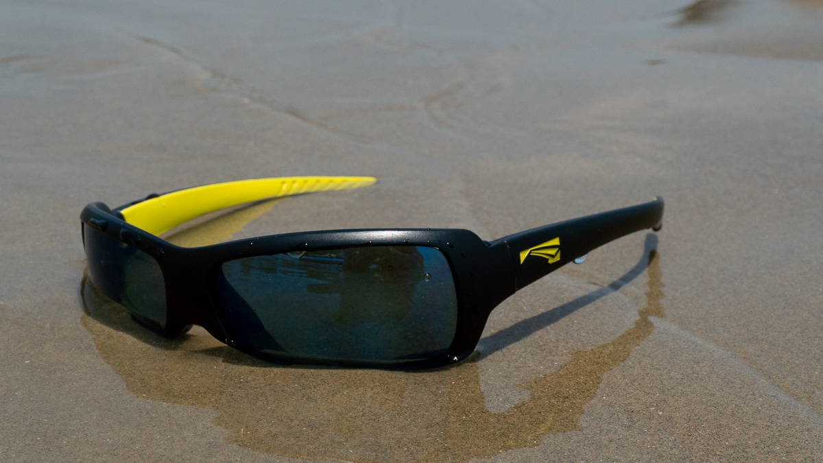 Black and yellow floating sunglasses semi submerged in water on sandy beach