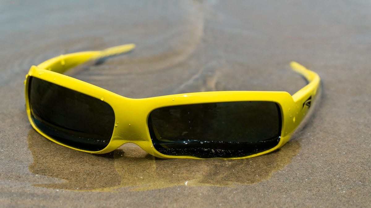 yellow floating sunglasses semi submerged underwater on sandy beach