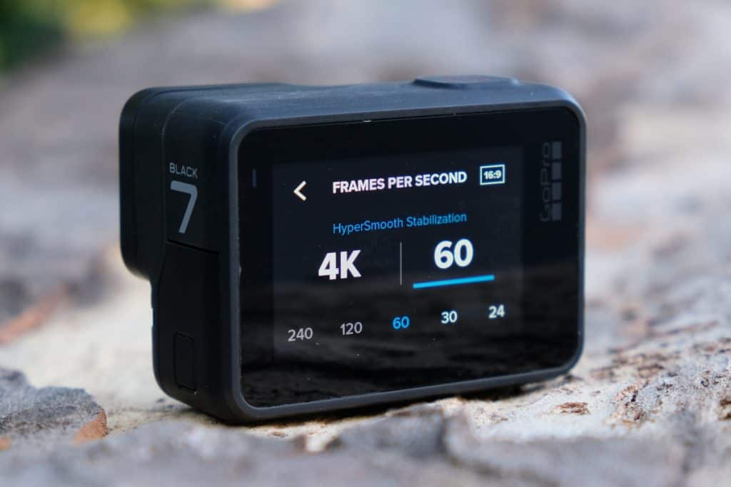 "a close up of a gopro with the screen showing the interface to choose image resolution. the screen reads ""4k / 60 fmps"""