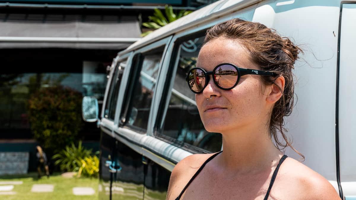 Femme portant des lunettes de soleil avec des lentilles Zeiss à côté d'un van VW