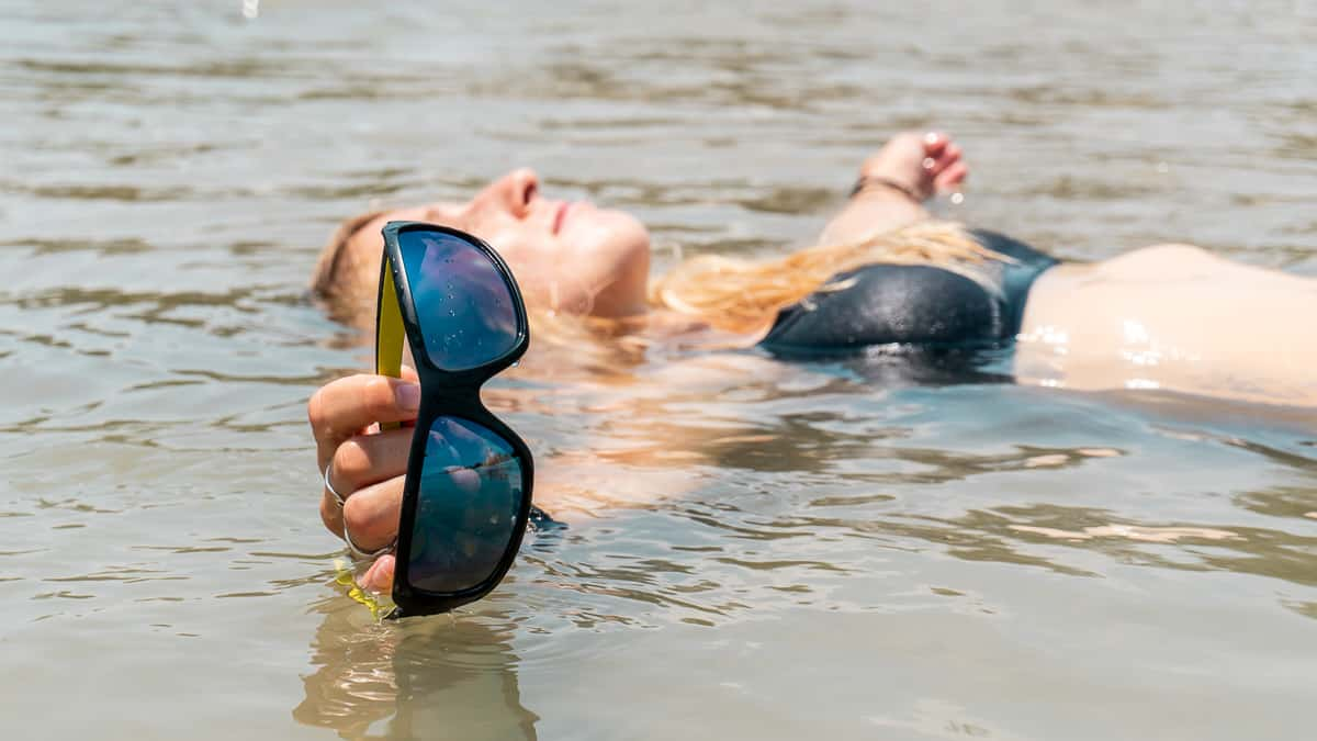 Julia Tausch lying in water with 'Flo' floating sunglasses in her hand