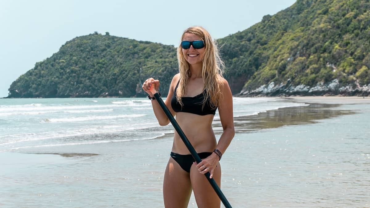 Blonde woman in black bikini paddling on an SUP and wearing LiP's new floating sunglasses