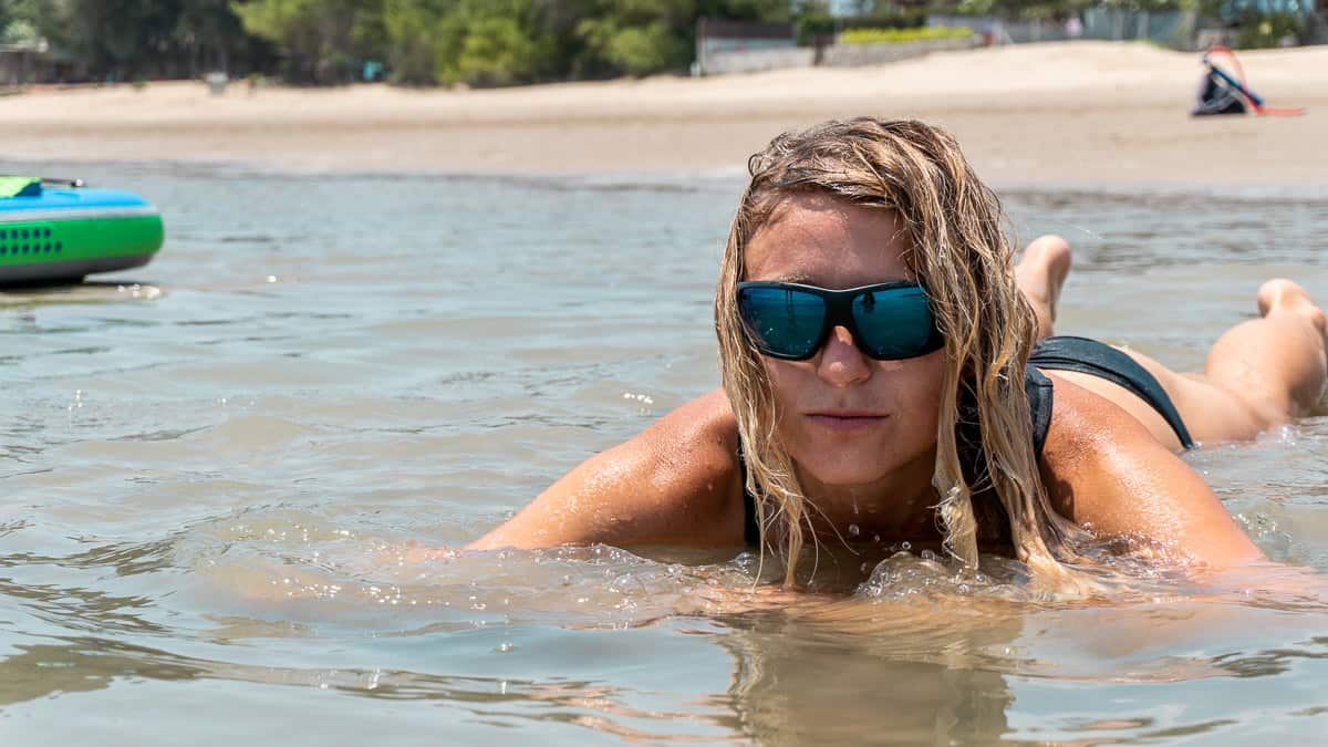 Blonde woman lying in water wearing dark coloured floating sunglasses by LiP