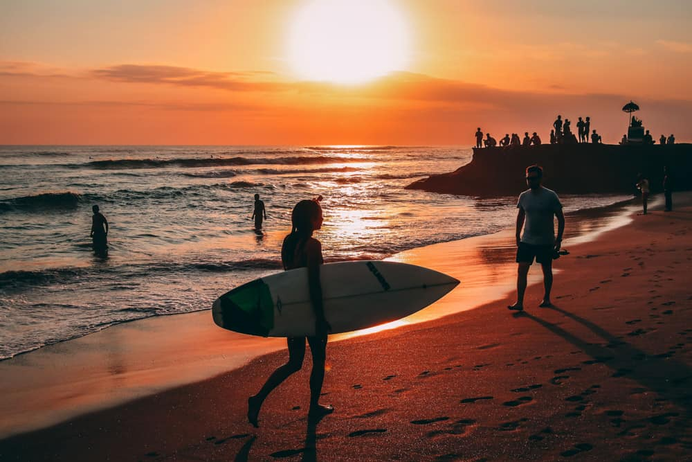Stunning sunset with surfer carrying surfboard across beach in Bali