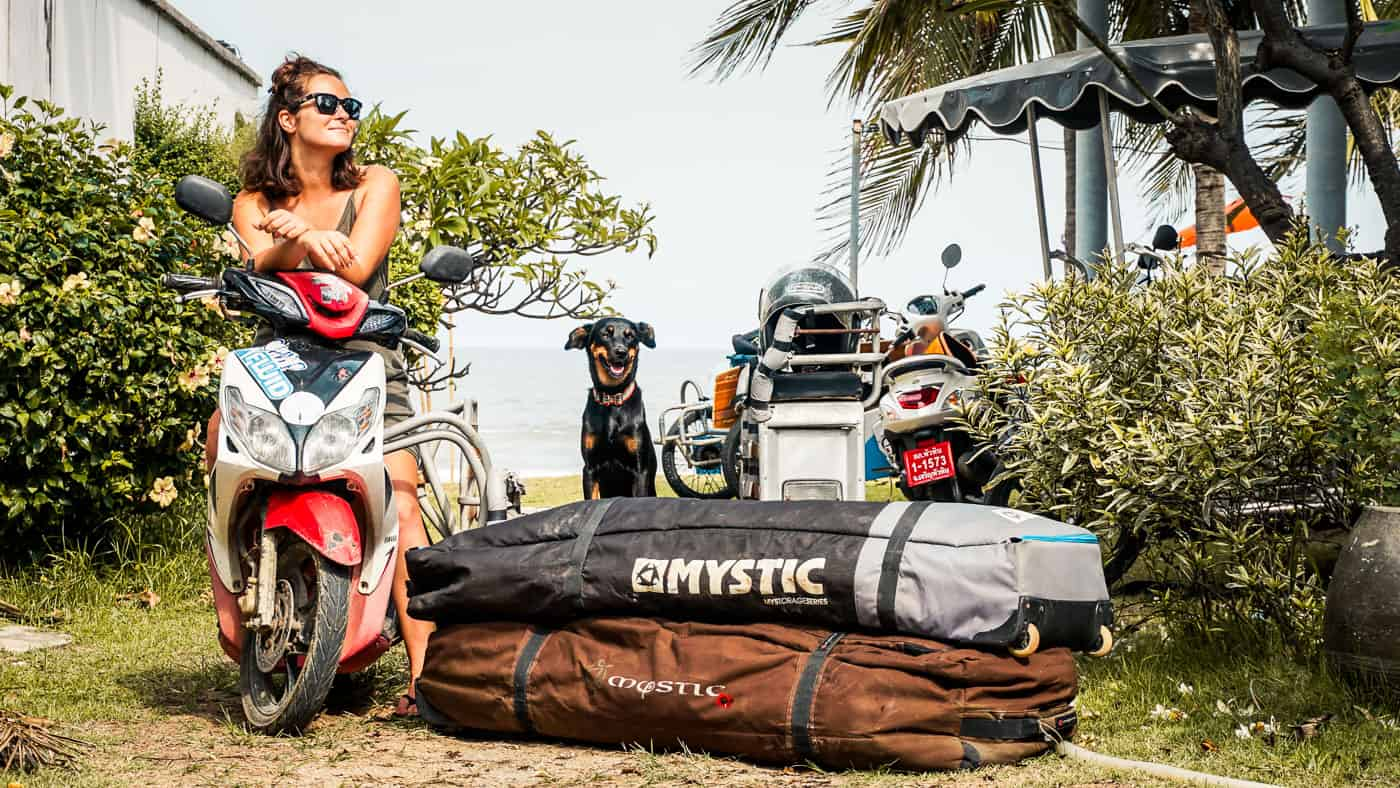 Two kiteboard bags loaded onto a saleng (sidecar in Thailand) driven by a lady and her dog