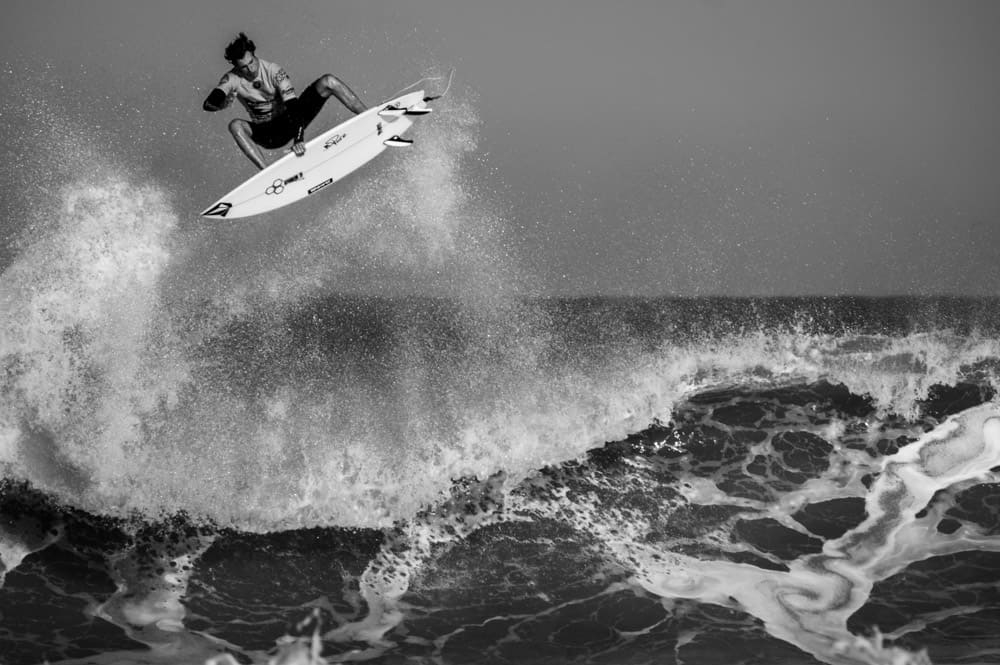 black and white surf photography of surfer flipping off the top of a rough wave