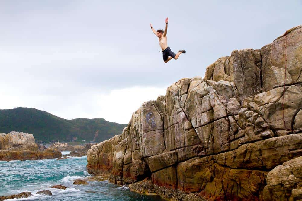 man jumping off cliff into ocean in Taiwan