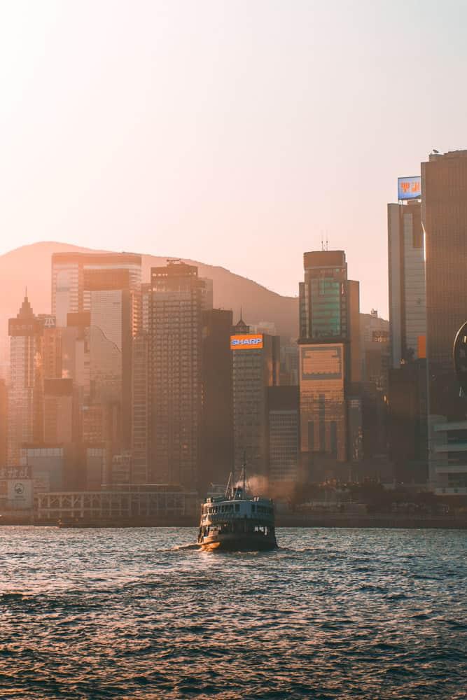 hong kong ferry approchng skyscraper-lined shore at sunset