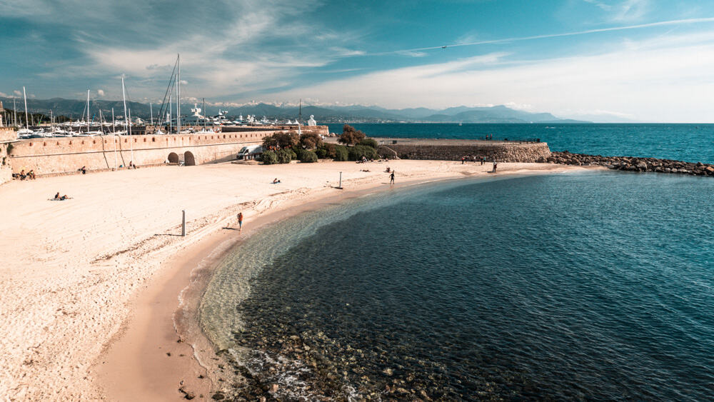 Antibes beach, with a crescent shaped strand and blue water hitting its shores. in the background, the yachts of the port vauban are bobbing in the water, and beyond snow capped mountains are just visible