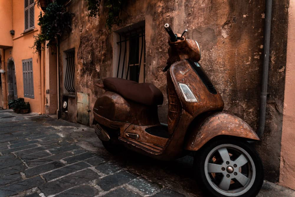 Rusty brown vespa parked in front of wall of same colour in Antibes Old Town
