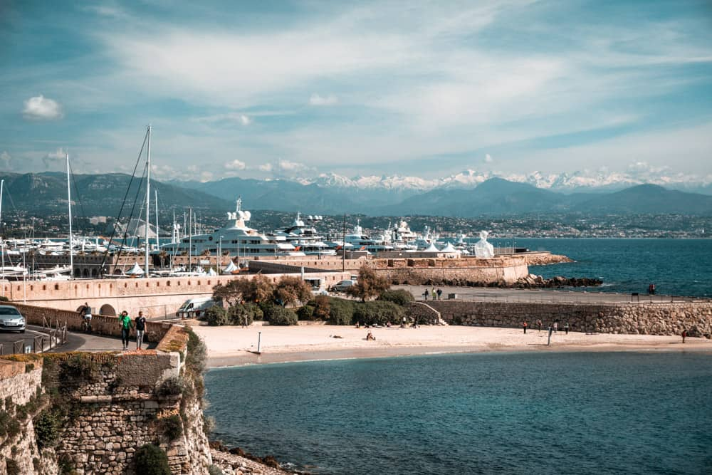 superyachts moored in Port Vauban (Antibes) with snow capped mountains in the background