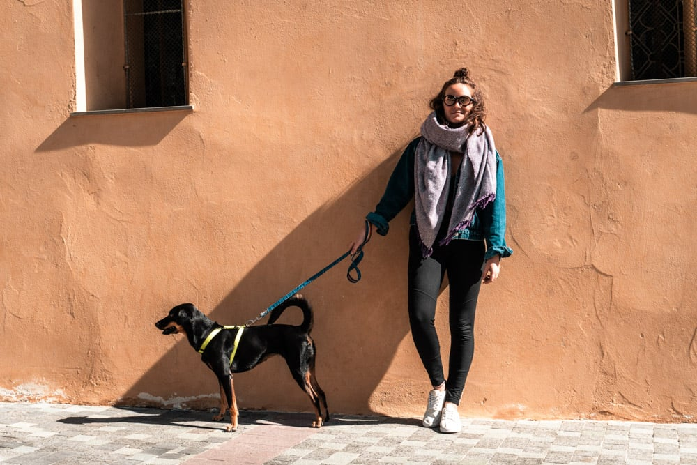 woman wearing sunglasses with dog on leash standing in front of terracotta wall in antibes old town, france
