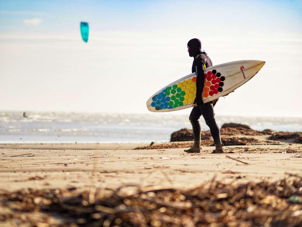 homme portant une combinaison de plongée avec capuche complète et transportant une planche de surf sur une plage de kitesurf