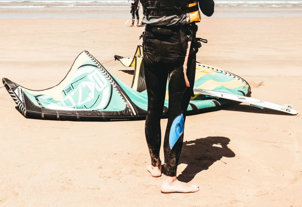 lower half of man's body wearing wetsuit as he prepares for a kitesurfing session