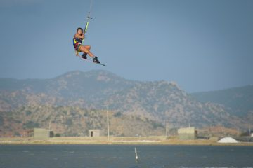 Aya Oshima jumping big on her kite with a twin tip board and boots. There are dusty looking mountains n the background