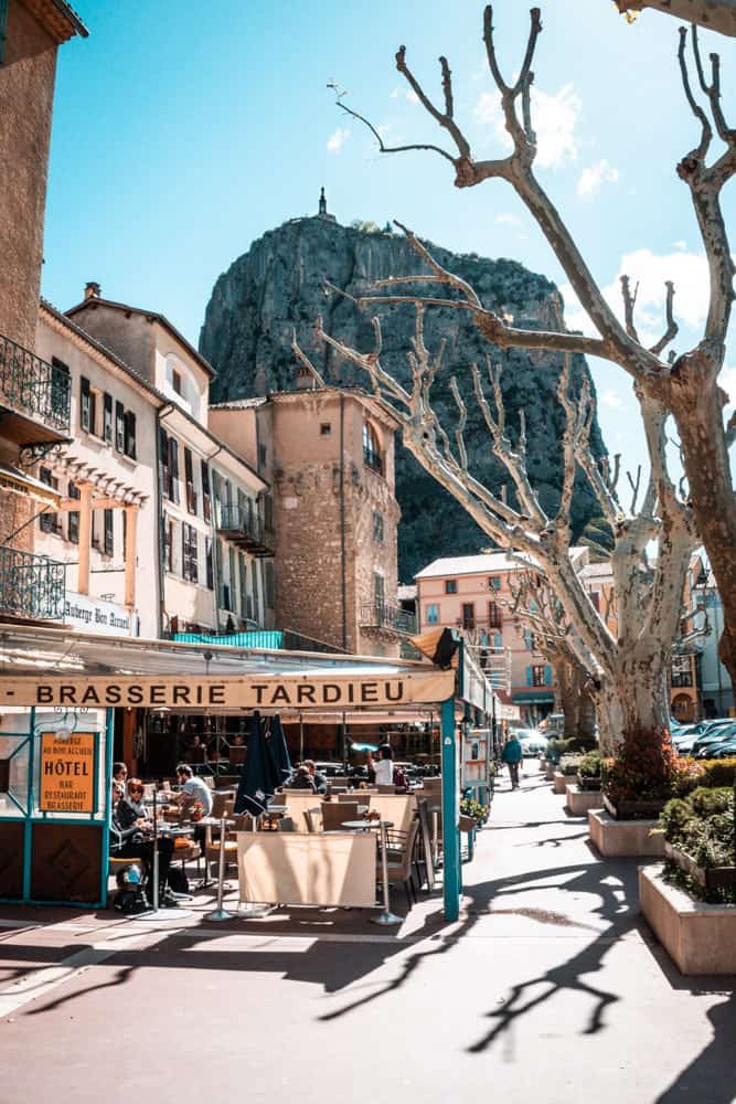 Castellane town at street level, south of france. In the foreground there are chalky beech trees and a cafe (brasserie). In the background there is a high cliff with a chapel perched on top.