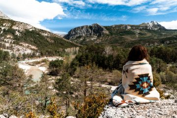 Woman wrapped in blanket facing the mountains just outside of Castellane, South of France