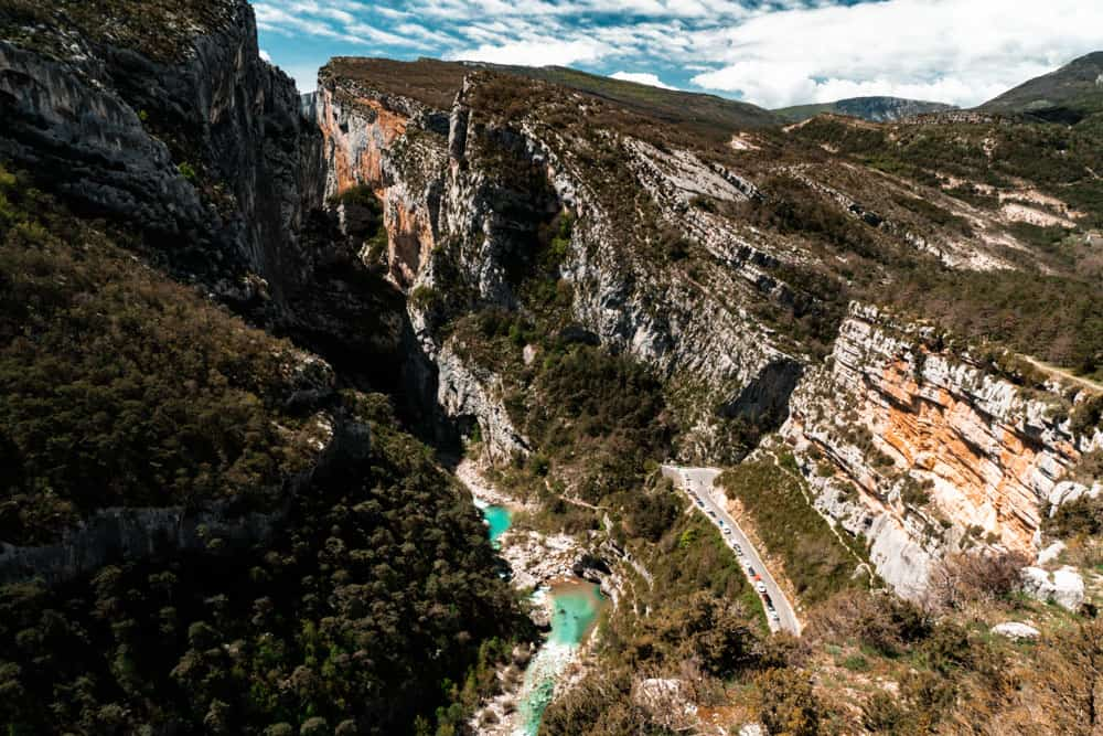 The Verdon gorge from the lookout 'Point Sublime' which runs nearby the route napoleon. The gorge is bisected by a turquoise river, a blue sky overhead.
