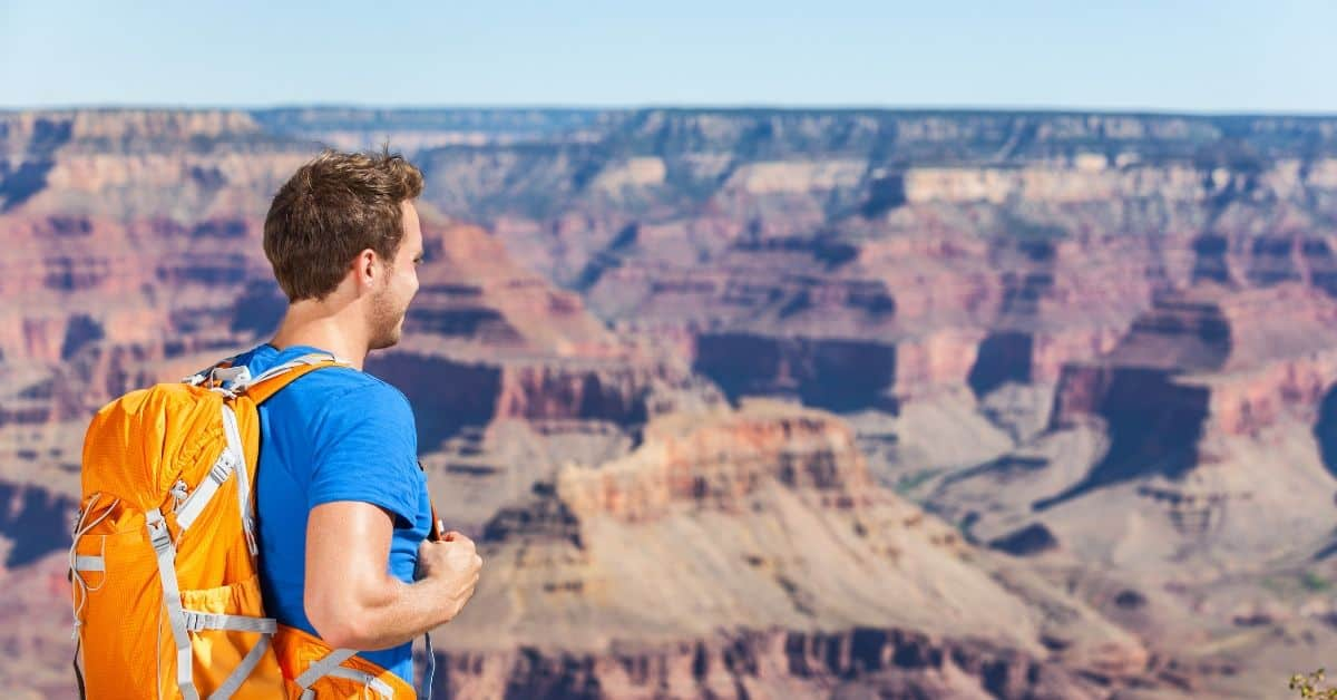 very sharp image of a young man wearing a bright blue tshirt and an orange backpack as he sets out for a day of hiking the grand canyon rim to rim. Behind him we see the showdy blue and red landscape of the grand canyon.