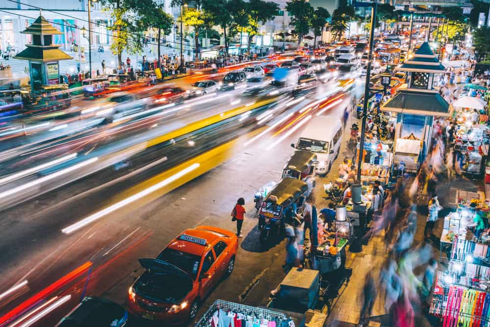 Long exposure at nighttime on a busy street in Bangkok. we see the blur of fast moving cars driving down the street and a bustling night market on the right.