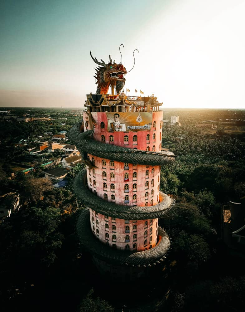 famous pink dragon temple in bangkok: a pink cylindrical skyscraper with green dragon statue wrapped around it.