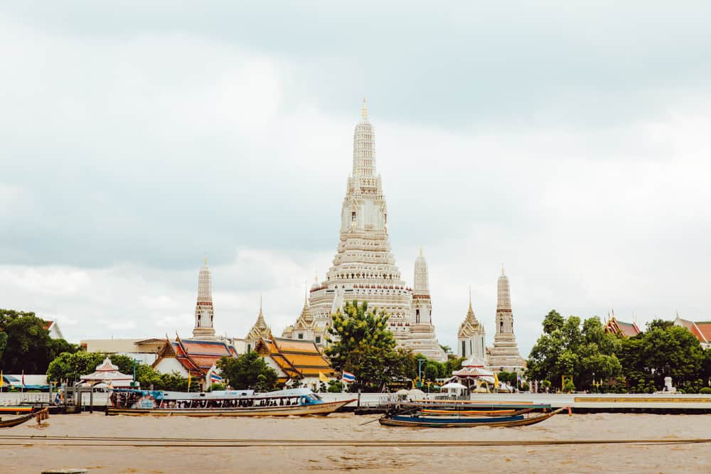 A huge white temple in Bangkok, with the river filled with colourful longboats in the foreground. Overcast grey sky above.