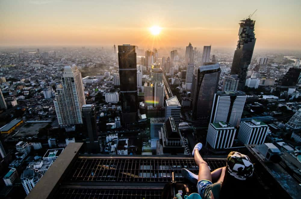 Sunrise over Bangkok: a woman in the foreground is sitting on a rooftop overlooking the skyscrapers of the city