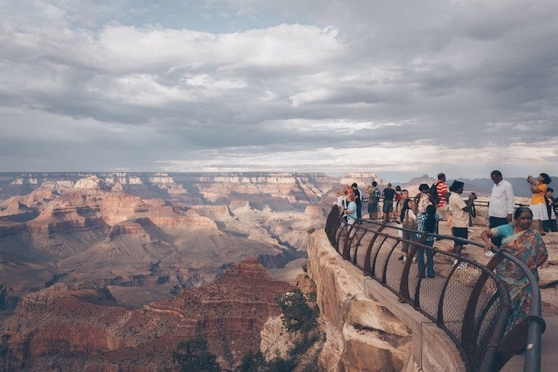 a gaggle of people stand on the right side of the frame on top of a viewpoint area, on the left side we see the hazy landscape of the grand canyon sprawling in every direction