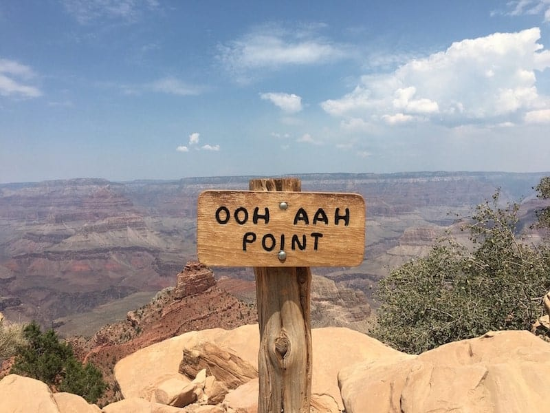 "a signpost in the foreground reads ""ooh aah point"" and in the background the hazy landscape of the grand canyon on a sunny day"