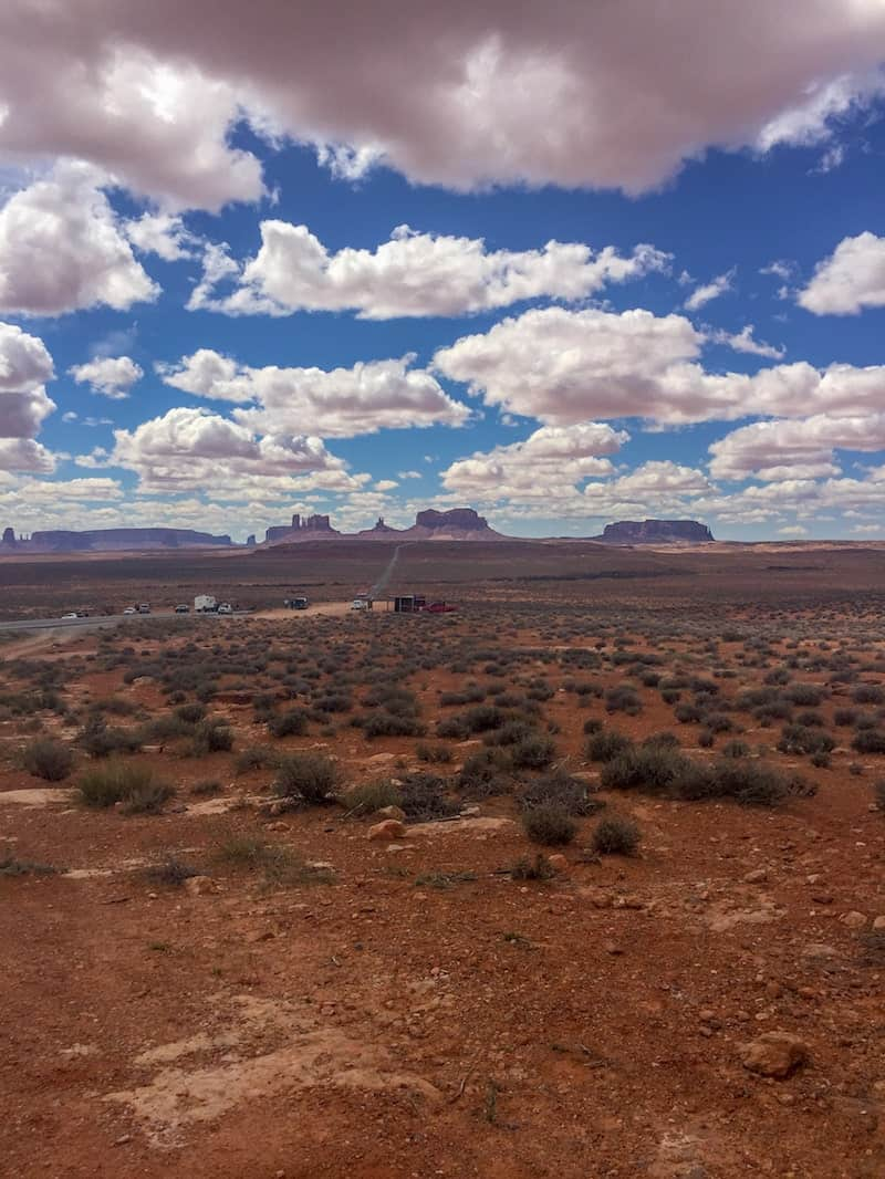 top of the picture is filled with blue sky and cotton candy clouds. on the horizon, the peaks of the grand canyon lay in wait. the bottom half of the picture is just red dirt and some rocks, with scraggly green tufts of grass growing here and there.