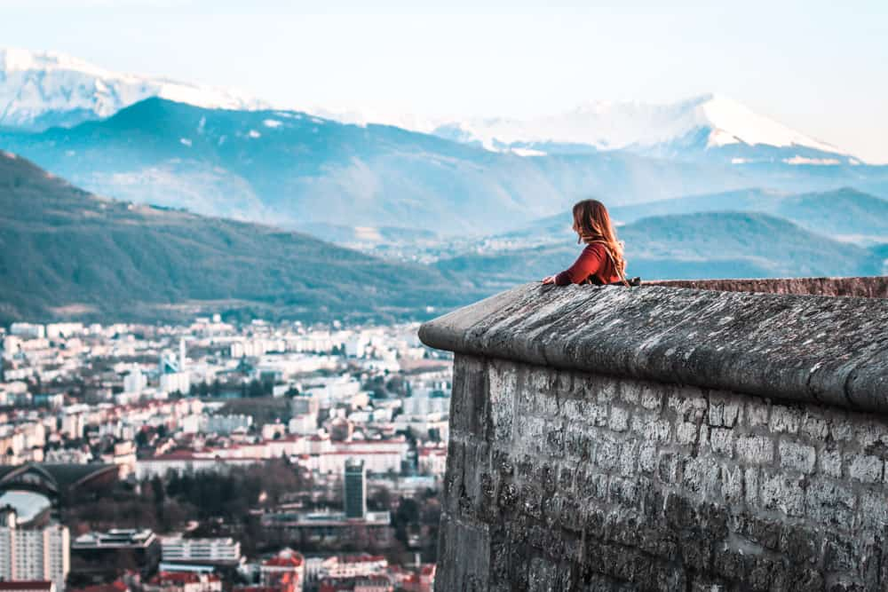 Girl looking over Grenoble from a wall above the city