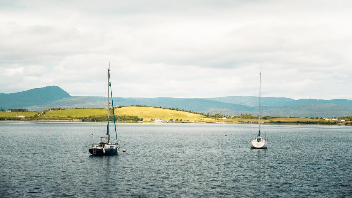 whiddy island on an overcast day, with two sailboats floating in the bay in the foreground