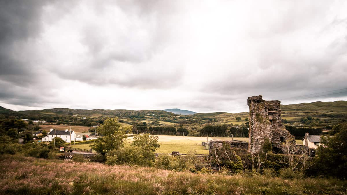 Carriganass Castle (in ruins) in the foreground, fields and farmland stretching to the horizon on a cloudy, moody day in west cork