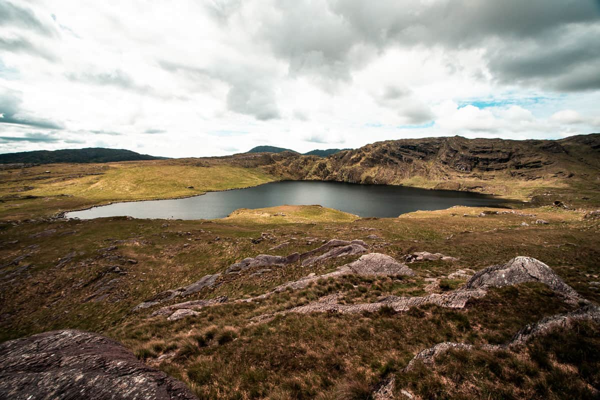 Moody scenery at Barley Lake, West Cork. The water on the lake is grey/black and shimmery in the soft light, clouds are in the sky overhead, rough grass surrounds the landscape