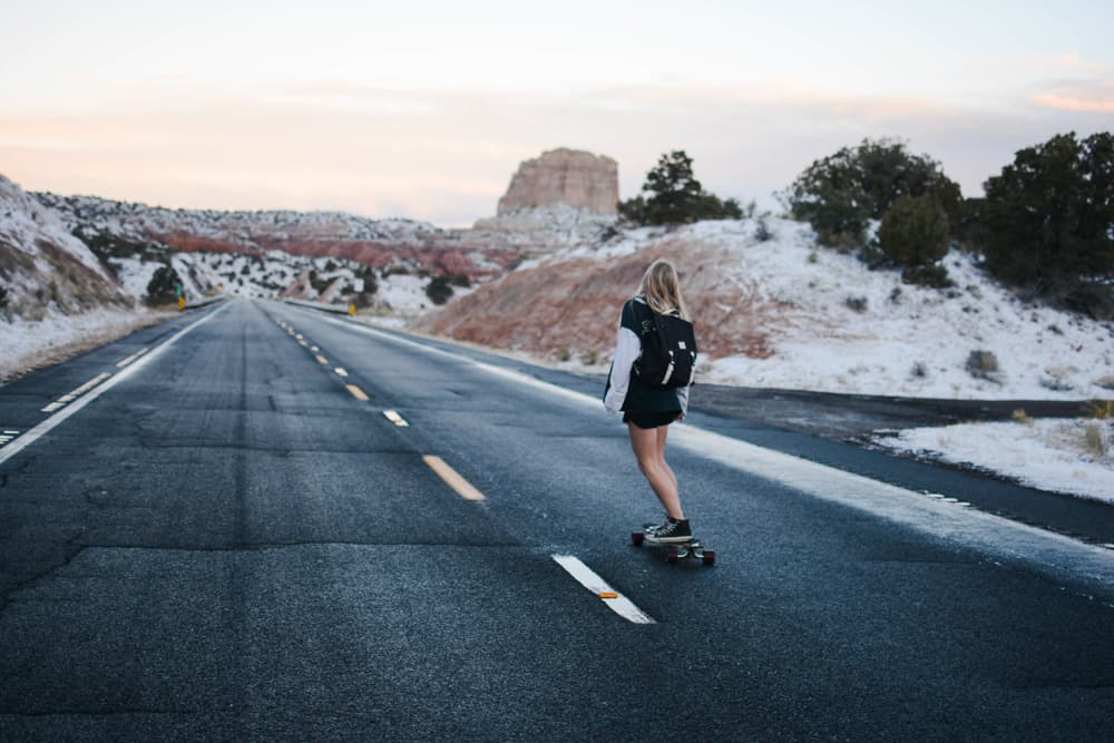 woman skateboarding down asphalt road with washed out rocky outcroppings in the background
