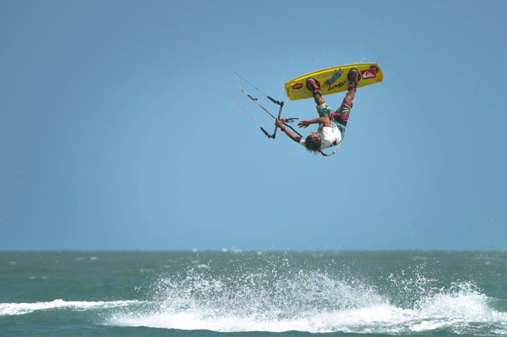 multiple times asian kitesurfing champion, 'yo' narapichit pudla, kitesurfing on thailand's blue waters. He's in the air, inverted, pulling a trick as water splashes below him.