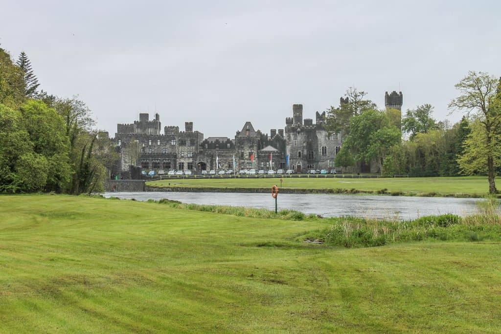 grassy manicured lawn in the foreground with ashford castle sitting just beyond a silvery pond in the background. a grey sky hangs overhead.